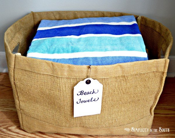 Linen closet organization by Simplicity In The South. Beach towel jute bin.