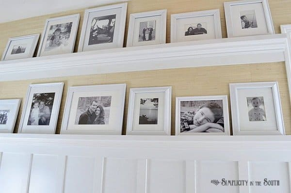 Need ideas for decorating your outdated hallway on a budget? This hallway was given board and batten wainscoting, DIY gallery wall shelves, new carriage style lighting, a DIY decorative air return cover and grasscloth