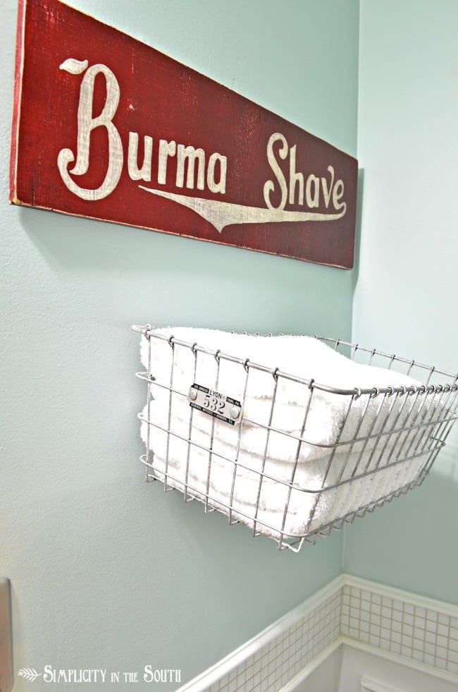 Wire basket to hold towels and a reproduction Burma Shave sign