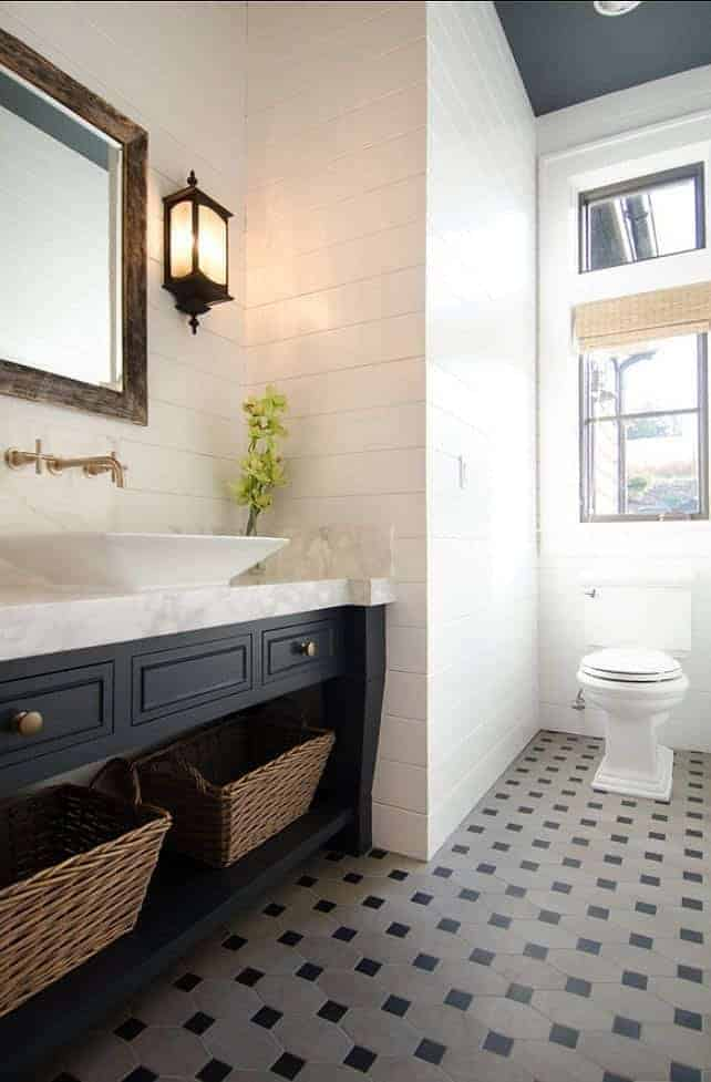 Navy and white bathroom with shiplap walls and salvaged wood mirror frame