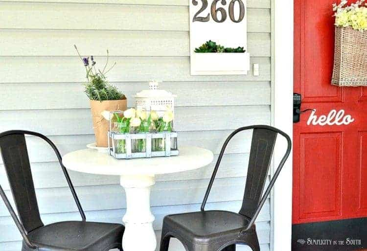 Reproduction Tolix chairs and a pedestal table makes a sweet place to enjoy your morning coffee on the front porch.