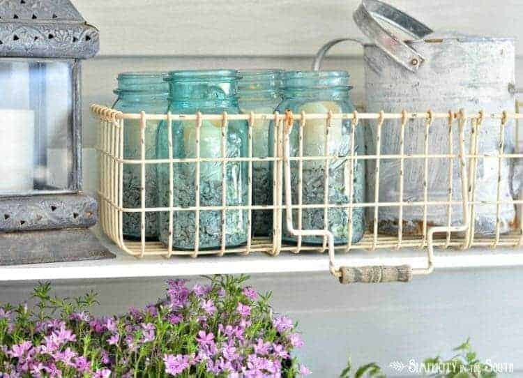 Need some ideas for decorating your front porch? By adding a repurposed bookshelf from inside the house, you can add plants, flowers, and even candles to welcome your guests.