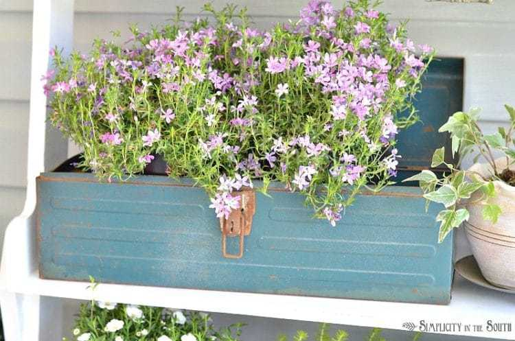 Repurposed teal tool box for flowers adds a touch of color. Need some ideas for decorating your front porch? By adding a repurposed bookshelf from inside the house, you can add plants, flowers, and even candles to welcome your guests.