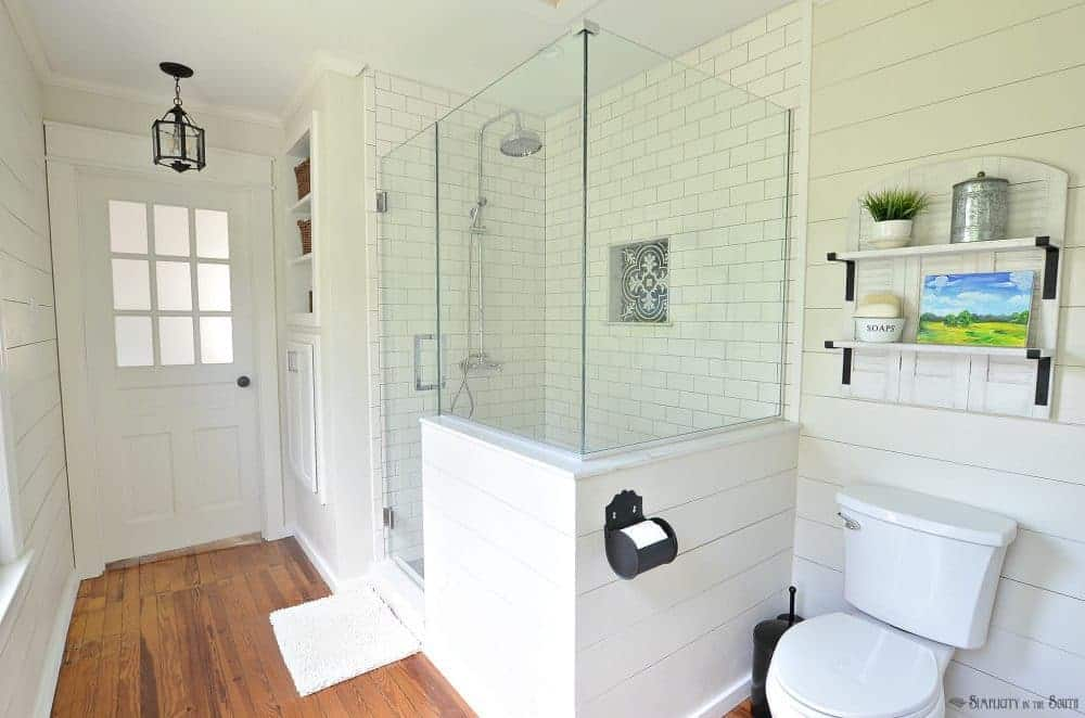 A modern farmhouse style bathroom remodel with glass shower enclosure and french door with frosted panels