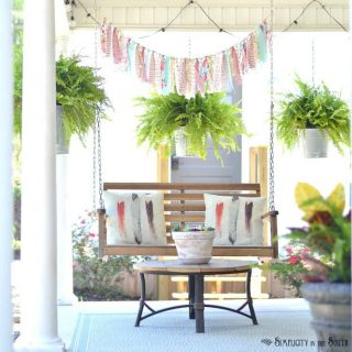 Summer front porch decorating ideas- Porch swing with rag and ribbon bunting and hanging pots with ferns in galvanized buckets