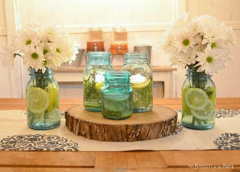 Mason jars with lemons, limes, rosemary, and essential oils to keep mosquitoes away