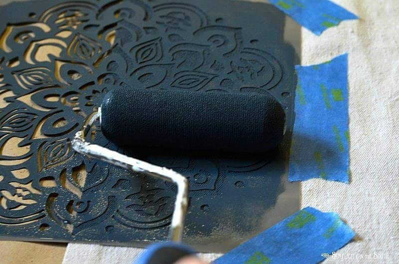 Tape stencil to drop cloth and use a sponge roller to apply paint