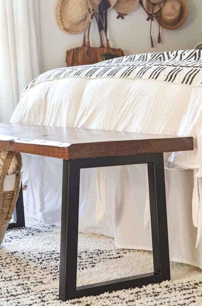 cedar bench at the end of the bed with modern black trapezoid steel legs
